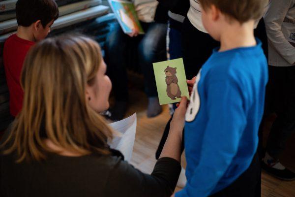 Poika ja nainen katsovat yhdessä korttia, jossa karhu näyttää suuttuneelta.