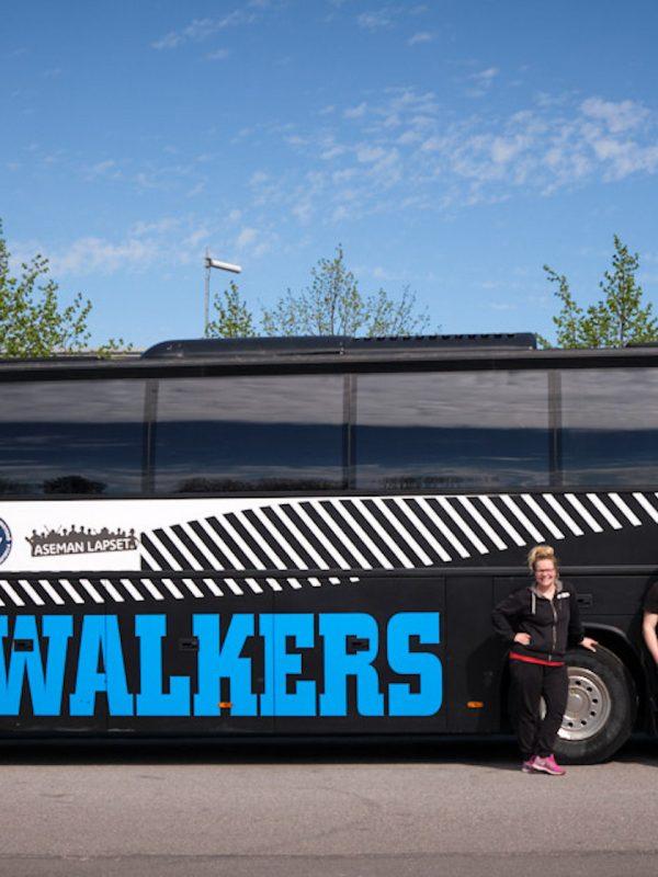 Walkers-bussi sivustapäin. Bussin edessä työntekijöitä seisomassa.