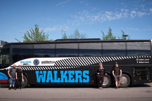 Walkers-bussi sivusta kuvattuna. Bussin edessä työntekijöitä seisomassa.