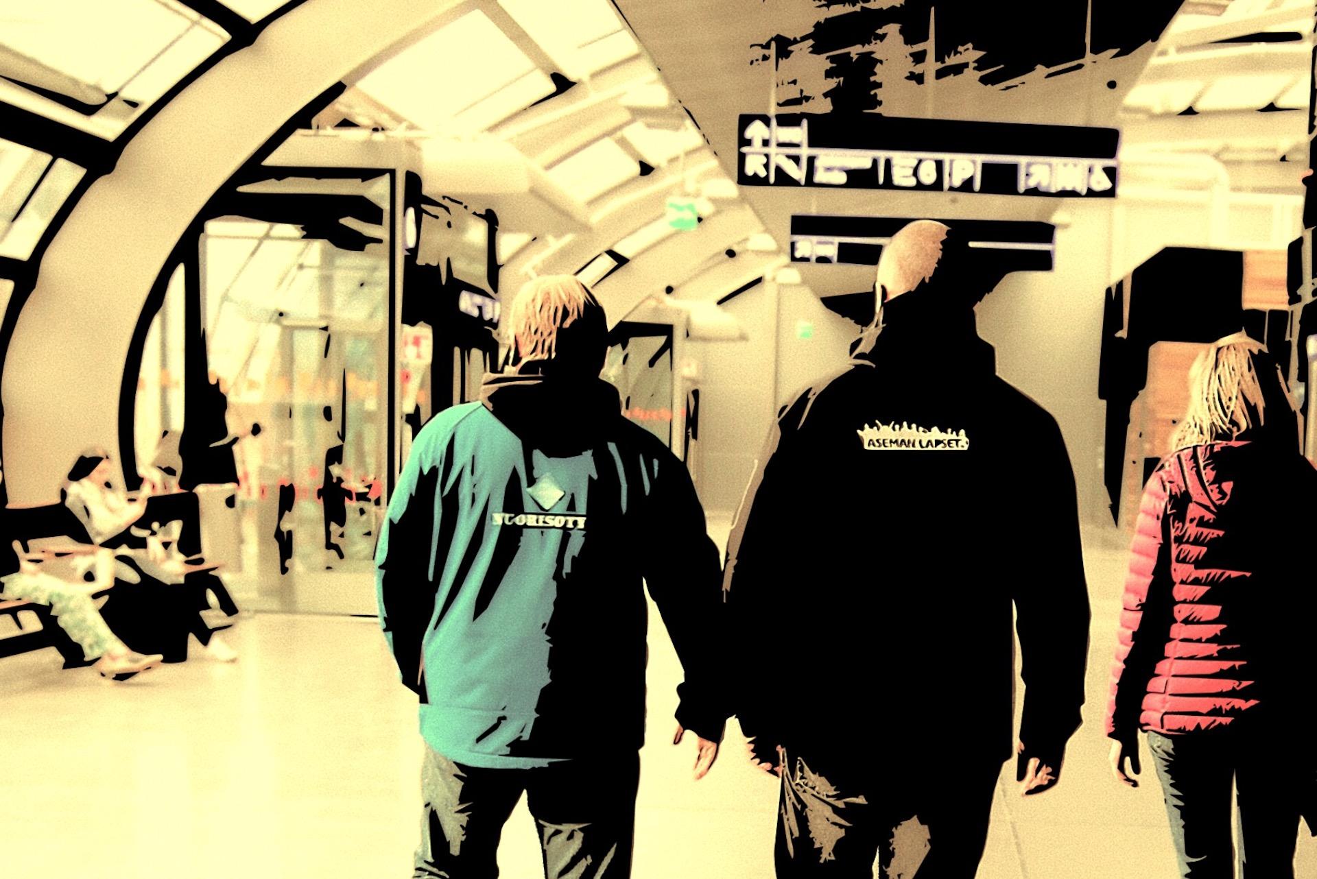 Kolme nuorisotyöntekijää kävelevät asemahallissa selkä katsojaan päin