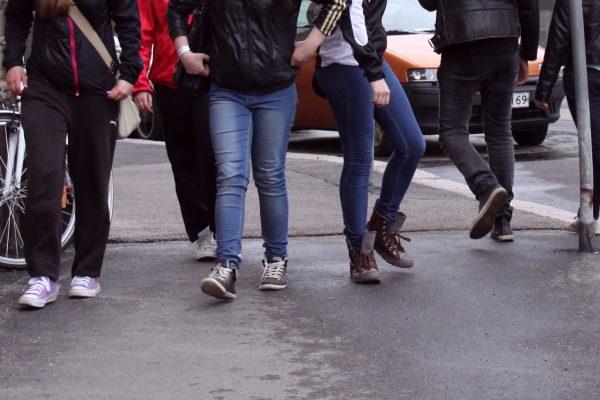 Nuorten porukka kävelee kaupungilla, kuvassa näkyy jalkoja.