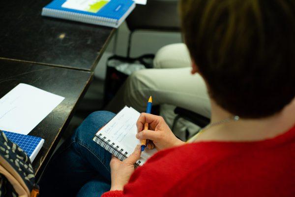 Henkilö istuu pöydän ääressä kädessään lehtiö, johon on kirjoittanut muistiinpanoja.