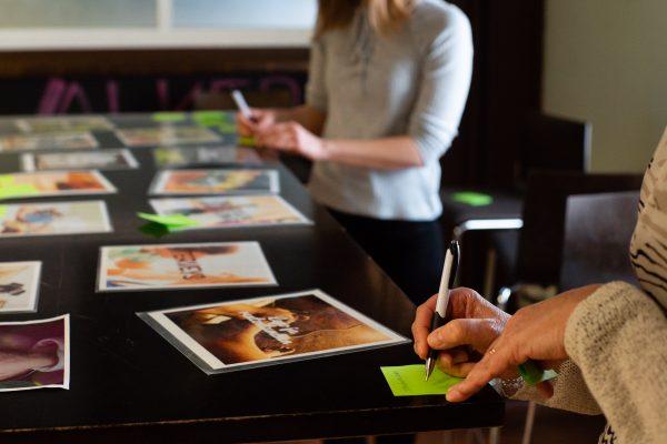 Kaksi henkilöä kirjoittaa muistiinpanoja pöydän ääressä, jossa on kuvakortteja.