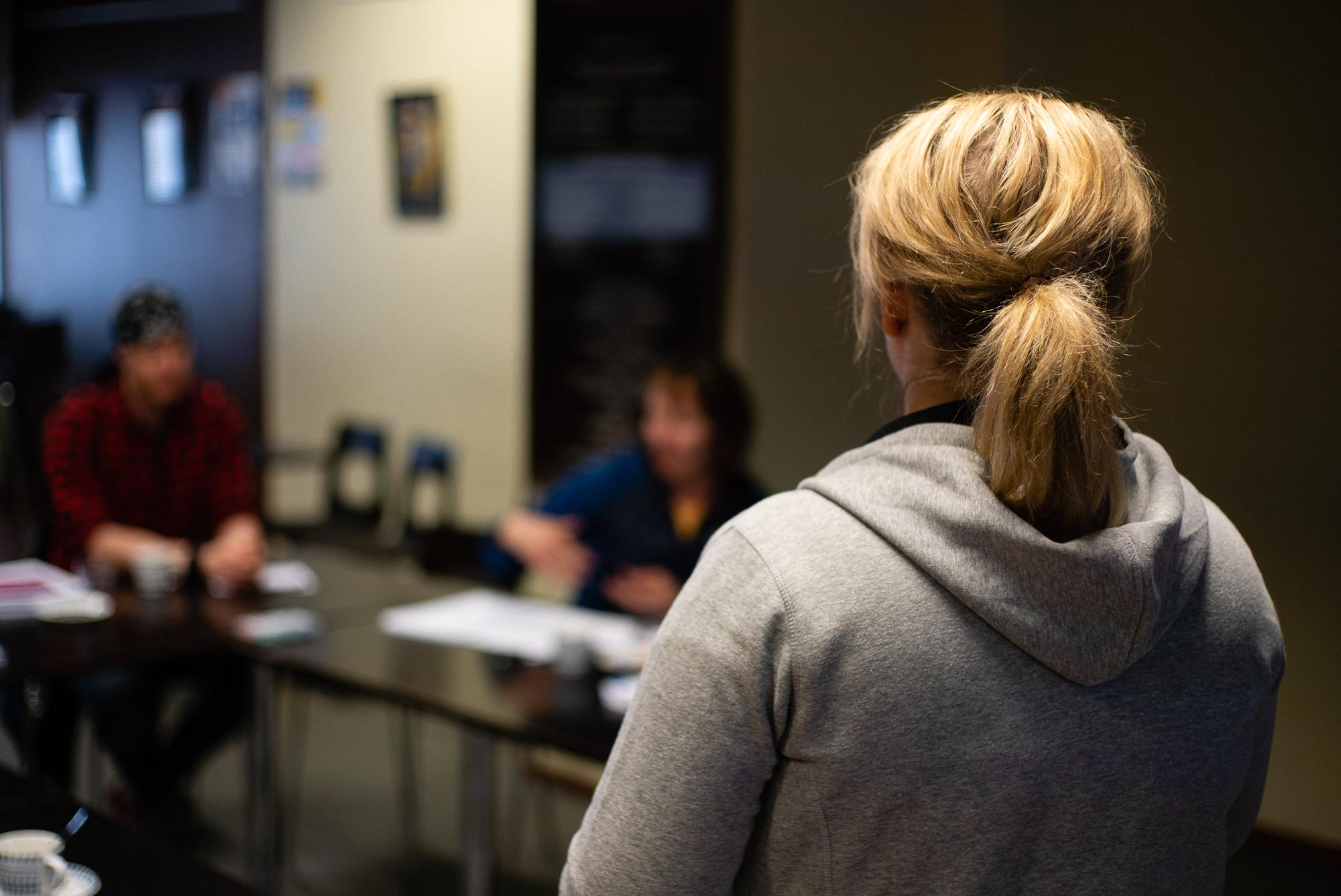Nainen seisoo selin kameraan, taustalla näkyy kaksi henkilöä istumassa pöytien ääressä.