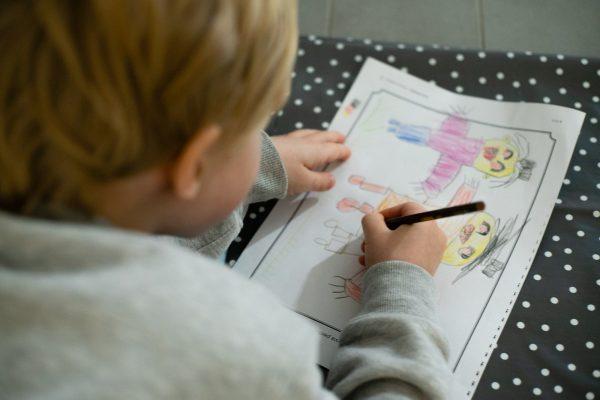 Pieni lapsi piirtää paperille kuvaa, jossa näkyy kolme ihmistä.