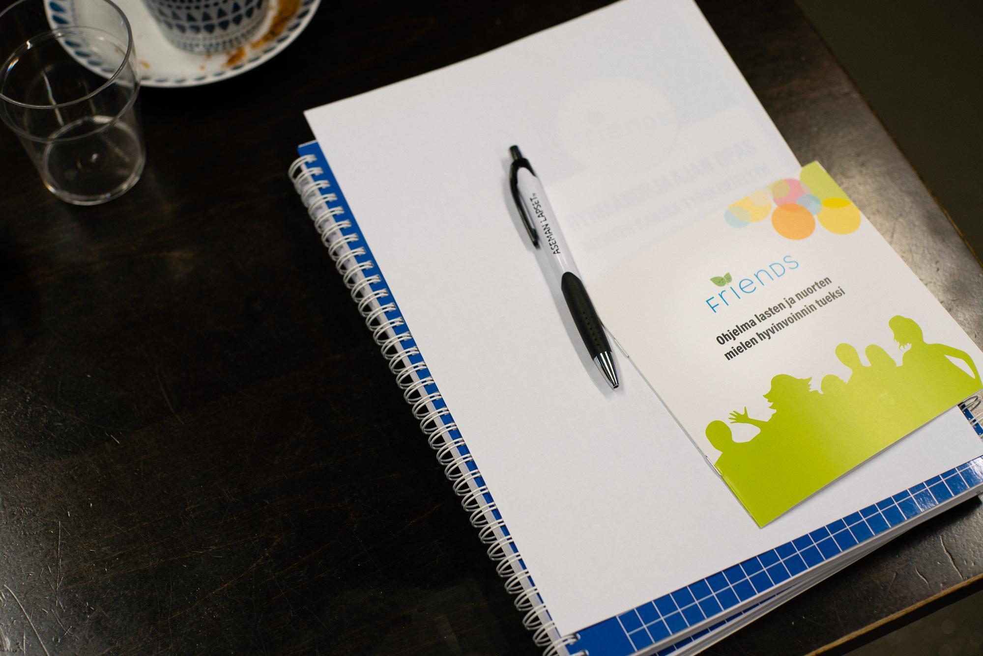 Lehtiö, kynä ja Friends-ohjelman esite pöydällä.