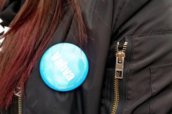 Tytön takissa rintamerkki, jossa lukee Vahva.