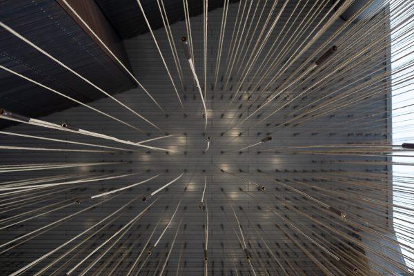 Kuvituskuva, jossa alhaalta päin kuvattu valaisin, jossa paljon lamppuja pitkien johtojen päissä.