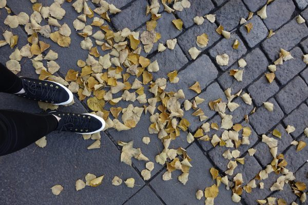 Kuvituskuva: mustat tennarit, keltaisia lehtiä maassa kadulla. Askel kohti tulevaa. Värikuva.