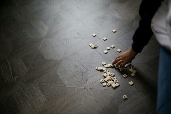Kuvituskuva, jossa pelinappuloita lattialla ja käsi niitä poimimassa