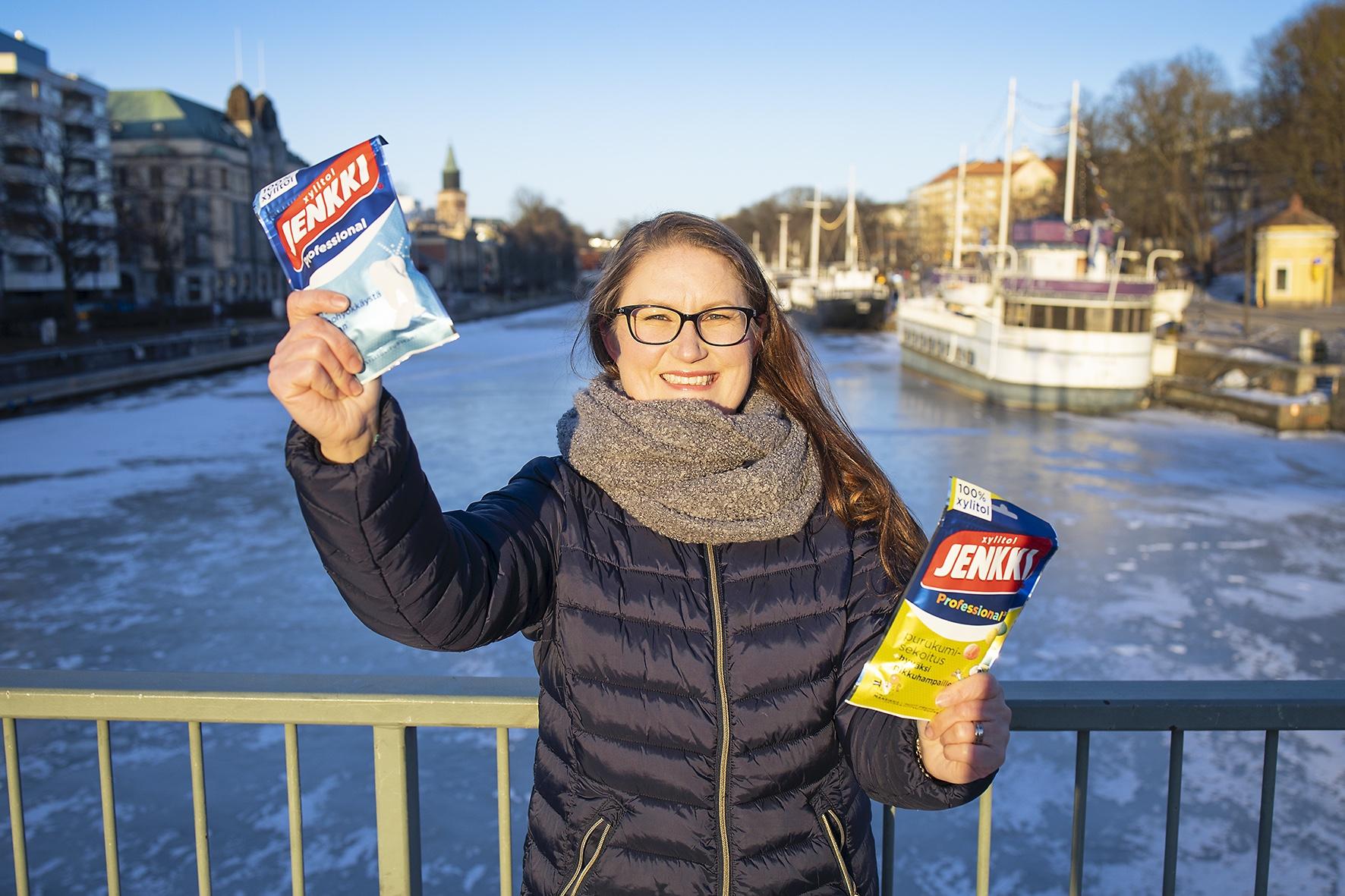 Ksylitolitiedottaja Milla Vihanto seisoo sillalla ja pitelee kädessään purkkapusseja.