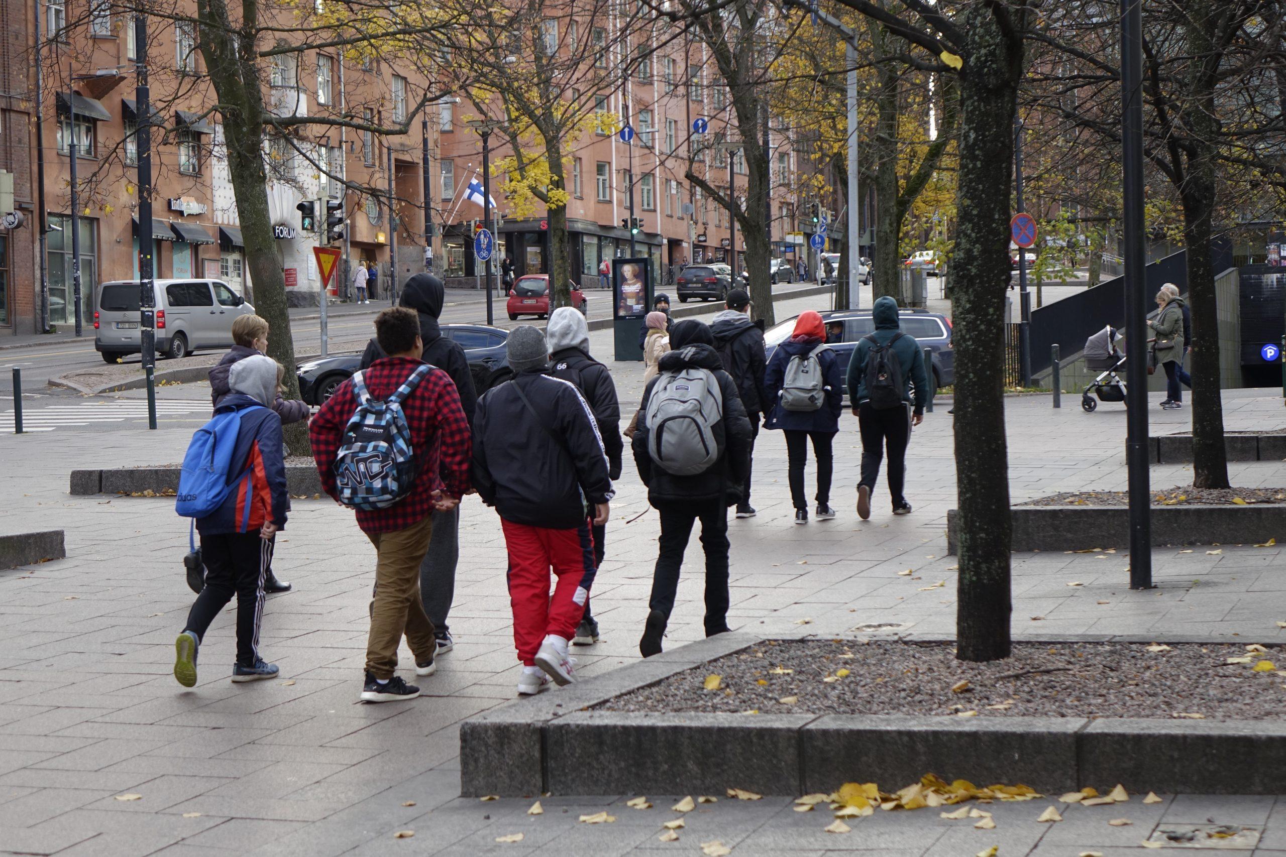Nuorten porukka kävelee Helsingissä Simonkatua. Kuvassa selin.