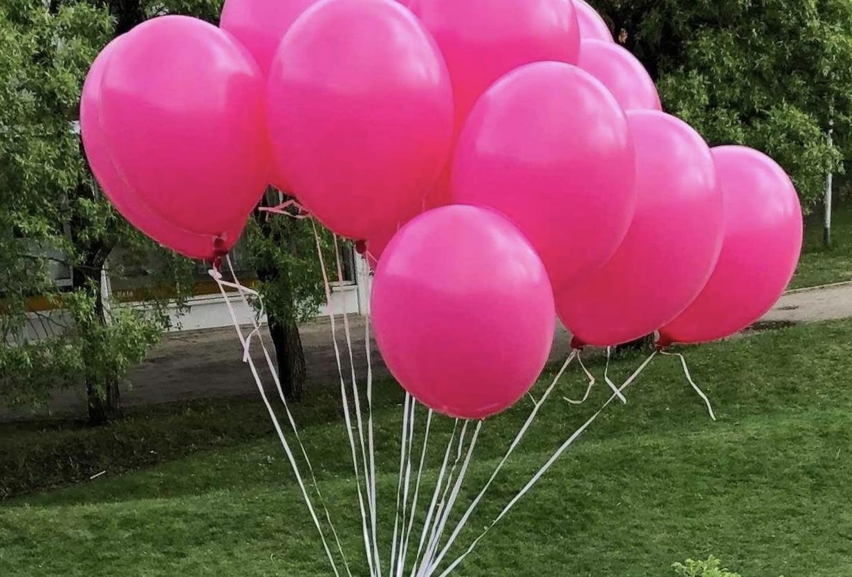 Vaaleanpunaisia ilmapalloja kimpussa vihreällä taustalla.