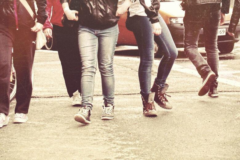 Kaupungilla kävelevien nuorten jalkoja. Kuvituskuva.