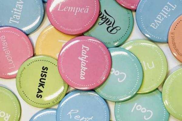 Eri värisiä Friends-pinssejä pöydällä. Pinsseissä on positiivisia adjektiiveja kuten