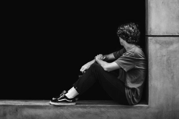 Mustavalkoinen kuva, jossa nuori mies istuu ja katsoo poispäin