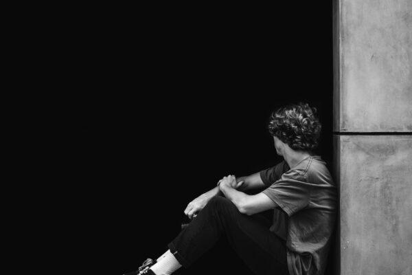 Mustavalkoinen kuva, jossa nuori mies istuu kasvot kameraan päin.