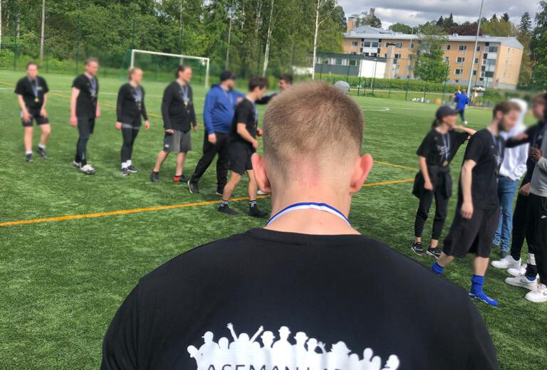 Pietro Saari selkä kameraan päin ja taustalla jalkapallon pelaajia kättelemässä