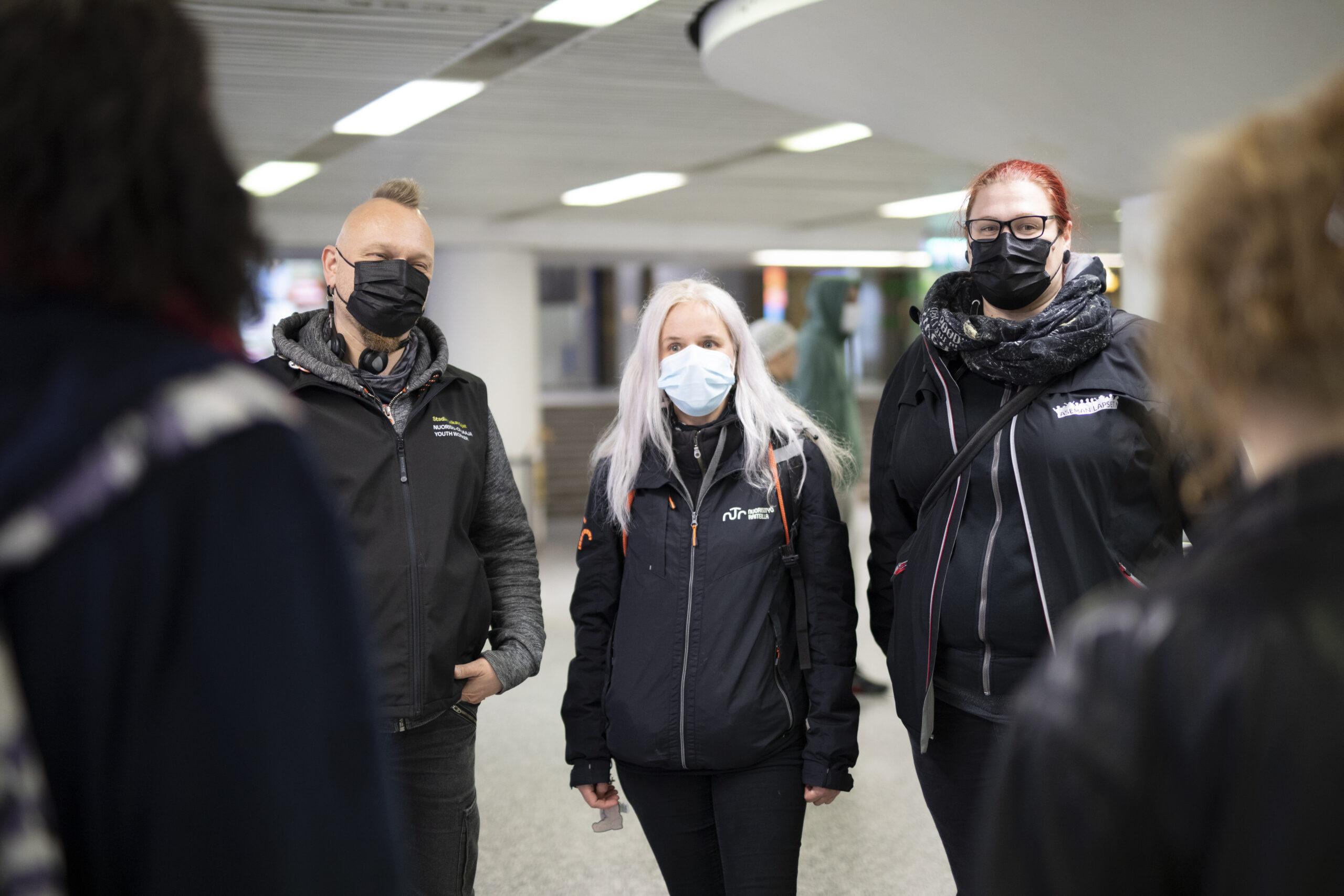 Kolme jalkautuvaa nuorisotyöntekijää seisoo asematunnelissa maskit päällä.