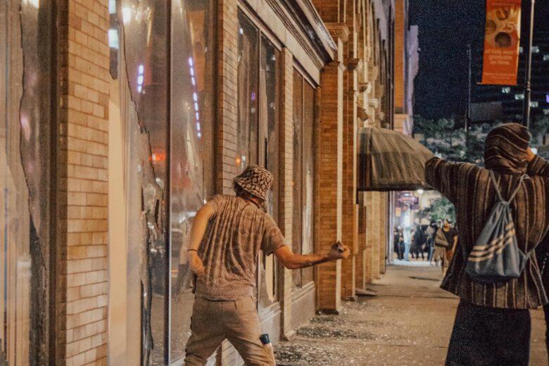 Kaksi nuorta hajottaa liiketilan ikkunaa