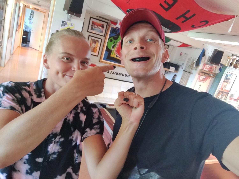 Kaksi henkilöä, joista toisella hammassuojat suussa ja toinen osoittaa häntä sormella ja nyrkillä