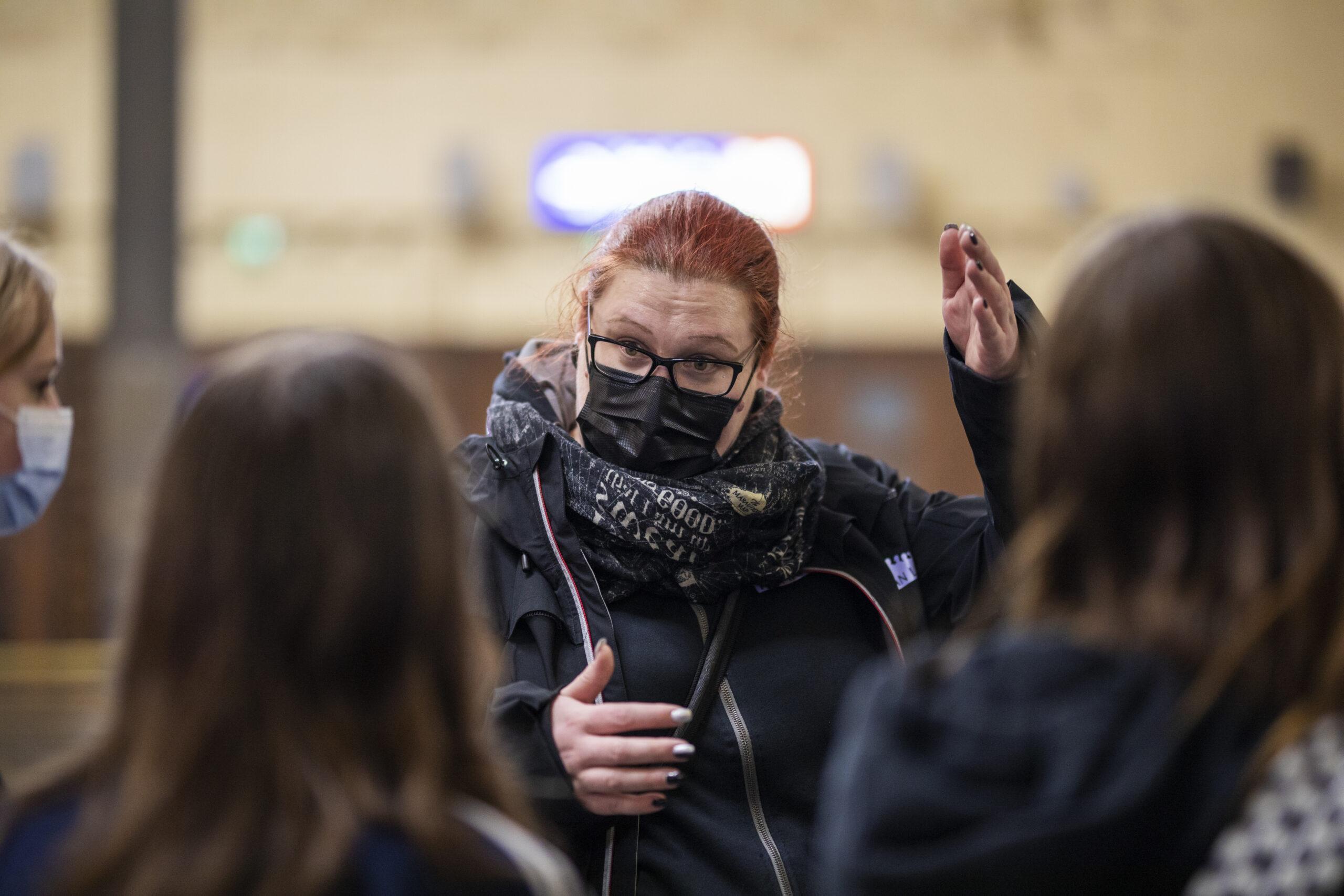 Turvallinen aikuinen juttelee nuorten kanssa, jotka ovat selin kameraan
