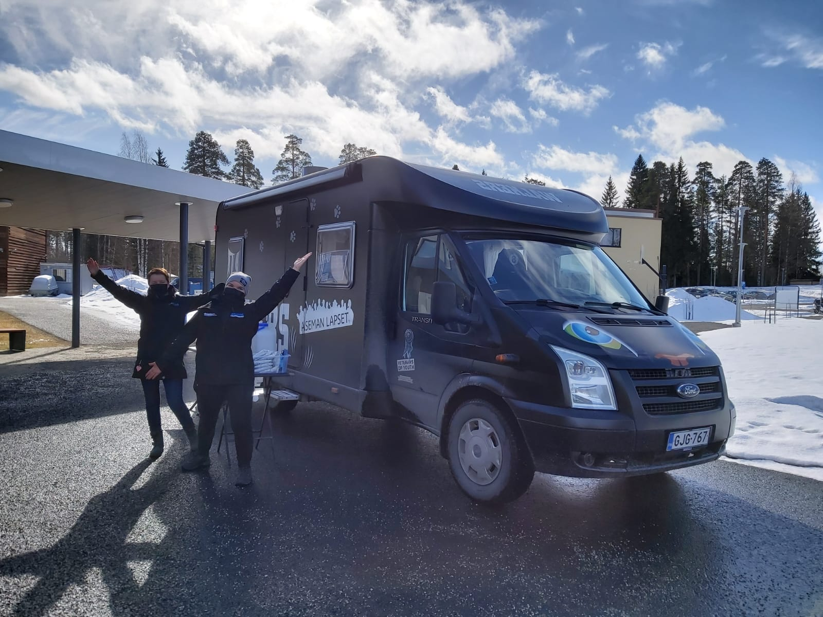 Kaksi nuorisotyöntekijää tumman matkailuauton edessä. Taaempana lumikinoksia. Kuva keväältä 2021 Varkaudesta.