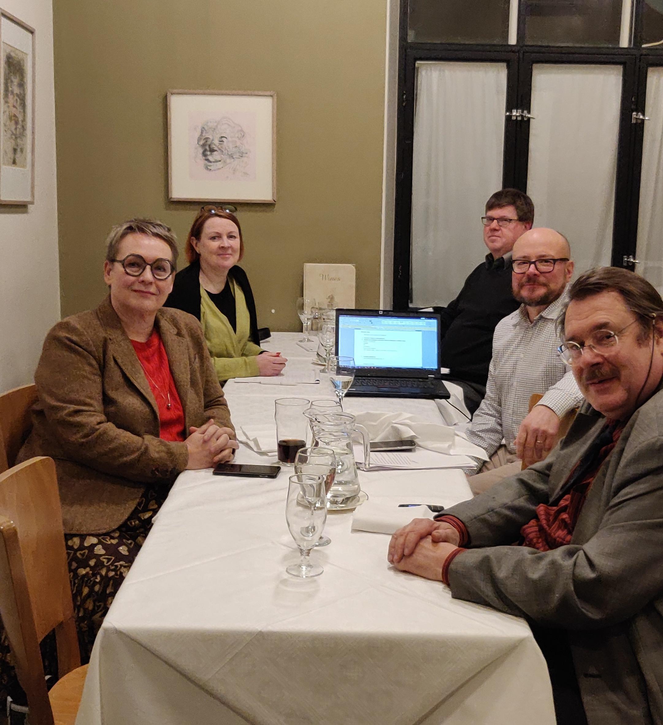 Viisi ihmistä istuu pöydässä ja katsoo kameraan.
